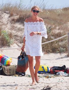 Olivia styled her Temptation Positano dress with a woven ombré beach bag, Dior cat-eye sunglasses, and a handful of her wear-with-anything accessories, including gold jewels and a black chunky watch.