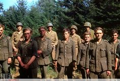 American troops stand guard behind German soldiers captured during the Normandy invasion, June 1944