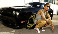 """When you have a single called """"Black and Yellow"""" that hit #1 on the charts I guess it makes sense to have a car to match. Wiz Khalifa posed next to his customized Dodge Challenger SRT8 in these recent photos and we have to say it looks pretty good. What do you think?"""