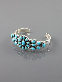 Sterling silver bracelet set with 23 sleeping beauty turquoise cabochons with a flower motif in the center.