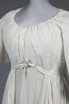 : A whitework embroidered open robe, circa 1785-95, embroidered with floral sprigs, the 3/4 length sleeves with latticed blind tuck pleating, un-boned English back, short front closing bodice panels, side ties to waist, trained skirt Condition Report: Good condition, extra small tri-angular section of cotton has been added to the centre back by the original owner who presumably put on weight, otherwise original and un-altered , a couple of small rust spots, good condition