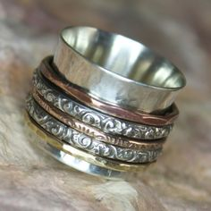 16mm Sterling Silver lightly textured band with 1 Copper, 1 Bronze, 1 Brass accent bands and 2 larger floral textured Sterling Silver spinner bands. All bands spin freely. Please add 1 size to your regular ring size to adjust for height. Learn about Sterling Silver and how to keep your item looking great, read my Additional Policies and FAQs https://www.etsy.com/shop/charmedlifedesigns/policy?ref=shopinfo_policies_leftnav To upgrade to Gold-Filled Bands: https:&#...