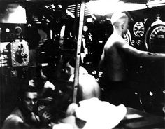 "Destroyer gunning, WAHOO running!January 27, 1943 - Wahoo's Control Room during ""Destroyer gunning, Wahoo running"" engagement. The boat has dived and is running silent. A string of depth charges has just exploded. Note the Planesman's shaved head from the ""crossing-the-line"" ceremony of days before."