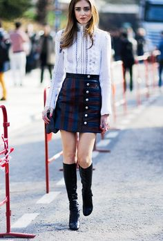 Chiara Ferragni wears a button-up mini skirt with a printed white blouse and black heeled boots.