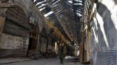 """A Syrian pro-government fighter walks past closed shops in the Bab al-Nasr district of Aleppo""""s Old City on 9 December 2016"""