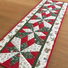 Christmas quilted Table Runner in green, red and pale cream festive foliage fabric with metallic gold highlights. Bring a touch of Christmas to your dining or kitchen table, sideboard or dresser. Ready to ship! table SewnByVicki shared a new photo on Etsy Christmas Table Mats, Quilted Table Runners Christmas, Patchwork Table Runner, Christmas Patchwork, Christmas Runner, Table Runner And Placemats, Table Runner Pattern, Holiday Tables, Xmas Table Runners