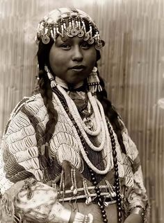 A Wishham Indian Bride. It was taken in 1910 by Edward S. Curtis.  She is wearing braids, beaded headdress with Chinese coins, dentalium shell earrings, beaded buckskin dress, beads around neck.