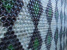 glass bottle wall...oh some day i would love to have an outside wall or table or somthing made out of colorful bottles that would catch the sun.....