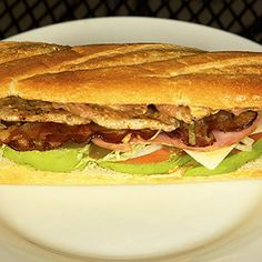 Three Little Pigs Torta    Pork loin, black forest ham and applewood smoked bacon served on a toasted French bread roll with beans, tomatoes, onions, jalapeño peppers, chipotle mayo, lettuce, Swiss cheese and avocado.  Find it at Manny's Tortas located inside the Food Building, on the east side.