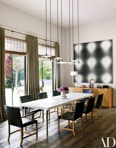 The great room also features vintage pendant lamps from Wyeth, an untitled Wayne Gonzales painting, a Corian-top steel table by Martin Szekely from Galerie Kreo, custom-made chairs by Roman Thomas, and a '50s sideboard by T. H. Robsjohn-Gibbings for Widdicomb | archdigest.com