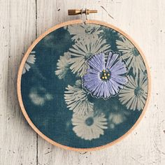 This unique, whimsical piece of art features a fabric cyanotype of an original photograph of wildflowers, displayed in a wooden embroidery