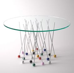 Table supported by giant pin-shaped legs.