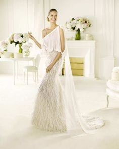This floor length one shoulder overlay is the perfect contrast to the feathered Vals wedding dress from Pronovias