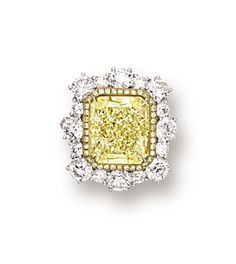FANCY YELLOW DIAMOND AND DIAMOND RING.  Centring on a cut-cornered rectangular modified brilliant-cut fancy yellow diamond weighing 7.39 carats, framed by circular-cut yellow diamonds and brilliant-cut diamonds, extending to the shoulders, the yellow diamonds and diamonds together weighing approximately 3.80 carats, mounted in 18 karat white and yellow gold.