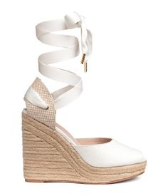 White. Espadrilles in cotton canvas with braided jute trim around soles, wide tie around ankle, and open toes. Faux leather lining and insoles. Rubber soles