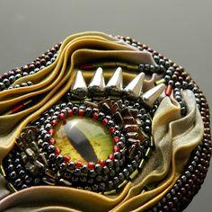 Dračí+pohled+Autorský+šperk+Brožka+je+vyrobena+časove+náročnou+technikou+šitého+šperku+a+korálkové+výšivky,+použit+je+skleněný+kabošon+s+motivek+dračího+oka,+který+je+obšívaný+kvalitními+japonskými+korálky+TOHO,+českými+korálky+preciosa+ornela,+brož+je+také+ozdobena+ručně+malovaným+hedvábímshibori+ribbon,+podšita+umělou+semiší+alcantara.