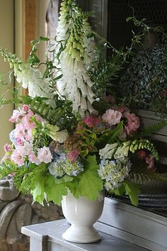 Foxgloves, newly blue hydrangeas, roses, spirea, curly willow, and huechera meld together in a cream ware urn to create seasonal tribute. Fronds of Autumn fern add texture and a whisper of Summer's bronzed hues. The hydrangeas are not completely blue, and their creamy centers pick up the cream color of the foxgloves.