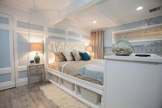 This Cape Cod master bedroom features a serene shoreline mural and pale hardwood floors. Intricate wall molding conceals a door to a large closet, and the custom cut-out headboard adds an organic pattern via interior lighting.