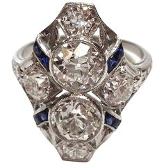 Art Deco Sapphire Diamond Ring. Period Art Deco diamond ring consisting of 2.20cts of diamonds and .70cts of blue sapphires. The two large diamonds in the center of the ring weigh approximately .90cts each, are european cut, have G-H color and VS-SI1 clarity (very clean). The mounting is in platinum and the ring is Circa. 1930-1940.