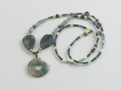 Moss Agate donut, leaves, and assorted shapes adorn this lovely necklace. For color, white and peacock fresh water pearls, blue onyx and green onyx