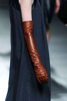 Ein minimalistischer Look: Lange Lederhandschuhe in cognac-Braun zu einem langen dunkelblauen schulterfreien Seidenkleid
