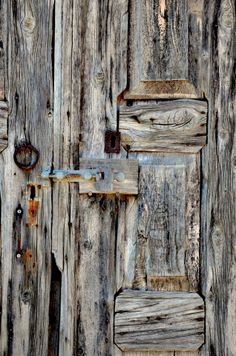 Weather-beaten - Section of an old, rustic, weather-beaten, wooden stable door in the village of Sianna, Rhodes. This door has endured a lot of hardships just like its owners: villagers who had to farm on hard, hostile terrain under a relentless sun.
