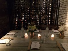 Gold Mason Jar vases and burlap-wrapped tea lights adorn this table in the Porch room, set for a rehearsal dinner