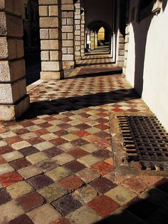 Covered sidewalk with colorful, old tiles in Conegliano, Italy north of Venice.