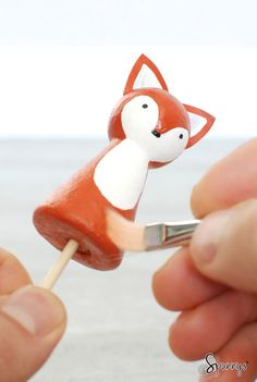 How to paint peg dolls. Here a spun cotton peg doll is held with a bamboo skewer for convenience and also to speed up the painting process. Use spun cotton peg dolls just like you would use wooden peg dolls. Painting theme: fox (woodland animals).