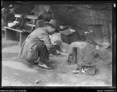 Unemployed man squatting and cooking in the Domain during the Great Depression, Sydney NSW, ca. 1930s