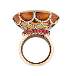 An oval cut Imperial topaz single-stone ring, in a circular-cut diamond lattice-work basket with a pave-set spinel collar,  mounted in 18kt white and rose gold the hoop with ceramic interior