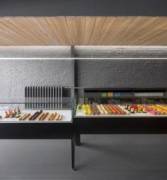 Colourful treats contrast with a black and grey interior inside this patisserie.