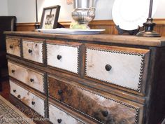 Creative Juices Decor: How to Decorate Using Animal Hides - dresser with animal hide glued on to fronts - use upholstery tack around it to give it a finished edge - LOVE this!