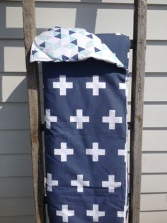 Navy cross reversible cot quilt with aqua, grey and navy triangles on reverse side. Measures 105cm x 90cm. Made with 100% cotton filled with a quilt insert. Perfect size for a play mat too! Washing instructions: Cold gentle machine wash. Do not tumble dry.