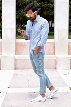 Shop this look on Lookastic: https://lookastic.com/men/looks/white-and-blue-dress-shirt-light-blue-skinny-jeans-white-low-top-sneakers/20259   — Yellow Sunglasses  — White and Blue Vertical Striped Dress Shirt  — Light Blue Skinny Jeans  — White Low Top Sneakers