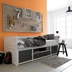 petite chambre enfant avec peinture murale couleur orange et lit avec des tiroirs