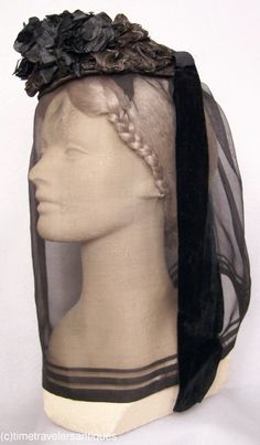 1865-1875 lady's Fanchon style woven horsehair and braided straw gimp mourning bonnet with a spray of black cloth flowers at the front. Silk velvet streamers, a silk drawstring lining with a wired buckram foundation, and a black silk mourning veil,  via eBay.