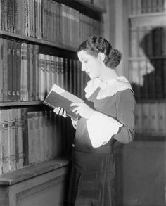 Lynn Fontanne, a British actress & major stage star, reading in library, 1928.