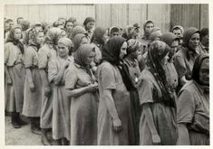 "Women fit for work after the delousing process. The disinfection of those not selected for the gas chambers, and the shaving of their heads, was all part of the ""registration""  process at the camp. After they finished, they were given the prison uniforms seen in the picture"