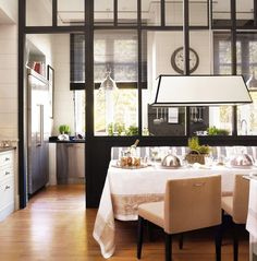 """Kitchens have a way to make my knees buckle. Make that a kitchen with a glass panelled wall and an adjoining dining area with a stylish banquette and I am bewitched.   This particular number fits under all of my """"wish list"""" categories: black windows (extra points for being indoor partition windows), white..."""
