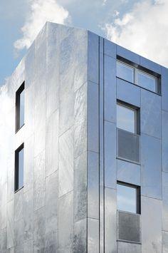 """Projektet består av två byggnadsvolymer uppbyggda kring samma tydliga lägenhetsstruktur. Den högre volymen som ligger mot gatan har en fasad bestående av """"dockskåp"""" – generösa balkonger i två etager som återspeglar lägenheternas innehåll. Volymen som ligger mot gränden är lägre och har en mer småskalig karaktär med uteplatser i en lägre nivå mot gatan. På...  Läs mera »"""