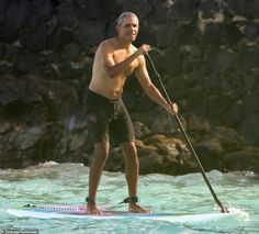 Swim trunk weather: Obama wore a black swimsuit with a ying-yang printed on the site. Barack Obama Pictures, Black Swim Trunks, Hawaii News Now, Marine Corps Bases, Malia And Sasha, Paddleboarding, Hawaii Vacation, Baby Girl Names, Former President