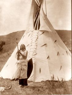 You are viewing an original photograph of a Sioux Indian Tipi.  The photo is by Curtis, and was taken in 1907. The picture shows Slow Bull in front of his dwelling.