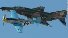 A jet-powered Vietnam War-era F-4 Phantom II flies in formation with a propeller-driven P-51 Mustang from the World War II era.