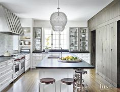 Walls were removed during the kitchen renovation to exude a more open feel. The space, designed by Mick De Giulio and Kathy Manzella of de Giulio Kitchen Design, includes custom cabinetry. Terzani pendants selected by Olive + Duke Interior Design create a focal point; the stools are from Bernhardt Design.