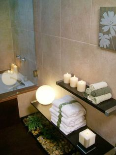 Low floating shelves display towels and candles making your bathroom a relaxing place to shower.: