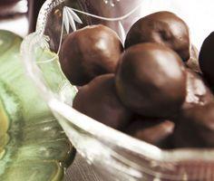 De här frukt- och nötgodingar är idealiska att servera på adventsfikat. Torkad frukt, mandel och pistagenötter marineras i glögg och därefter blandar du nötterna med saffran och havreflarn. Blandningen görs till små bollar som doppas i choklad. Mums!