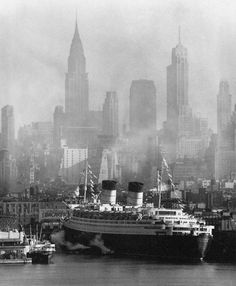 RMS Queen Elizabeth docked in New York Harbor. The New York Skyline in the background including the Chrysler Building.