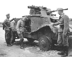 Germans examine a knocked out French armored car.