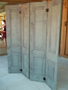 Salvaged doors, attached with door hinges, act as a room divider - Rhonda's Little House in Arkansas